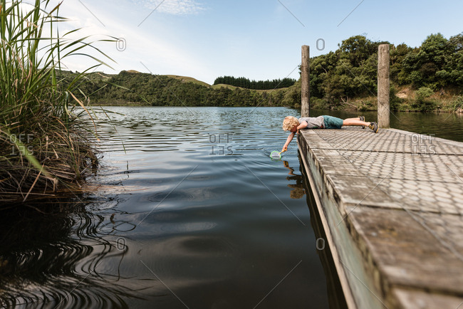 Toddler boy with a net reaching into a lake on a summer day