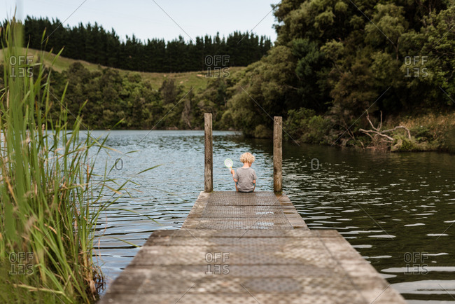 Young child holding a net at the end of a pier on a lake