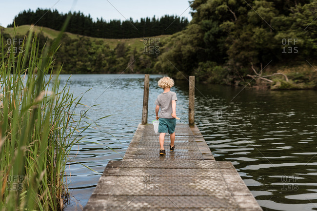 Small boy walking on a wooden pier at a pond