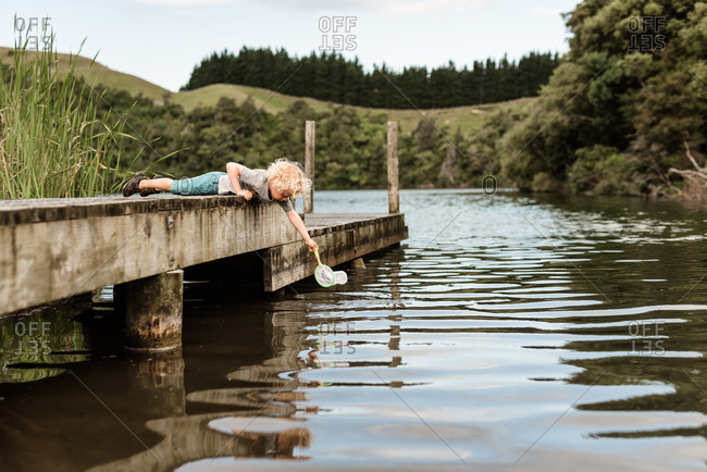 Young child reaching into a pond with a net