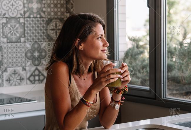 Caucasian girl is having a green vegetable juice in front of her big kitchen window.