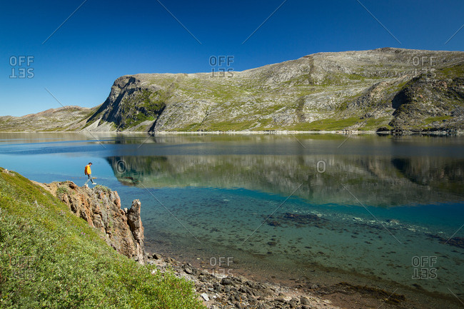 Person running along grassy shoreline on a sunny day in Torngats Mountains National Park