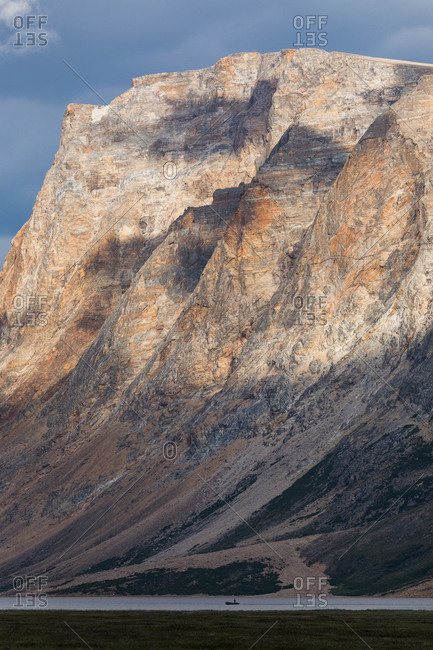 Small boat on water with mountain in background, Torngats Mountains National Park