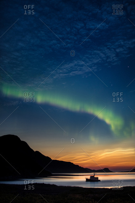 Aurora borealis and Noctilucent in the night sky over bay and boat; Torngats Mountains National Park