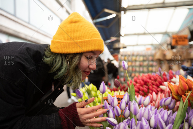 Young woman in yellow hat sniffing flowers in local florist.