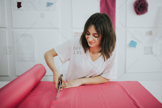 Fashion designer cutting a fabric with scissors.