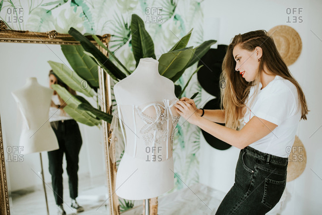 Fashion designer making a wedding dress in front of a mirror
