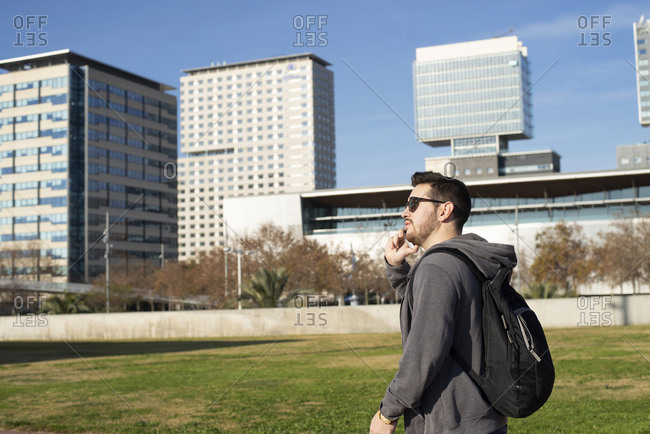 Side view of a Man using smart phone while walking against city buildings