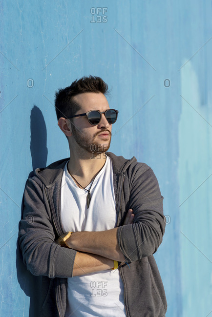 Portrait of young bearded man with sunglasses leaning against wall