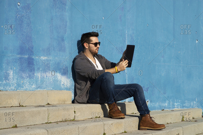Side view of a young man with sunglasses sitting on stairs while using a tablet pc