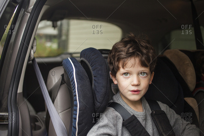 top half of a small child with direct gaze sitting in carseat in car