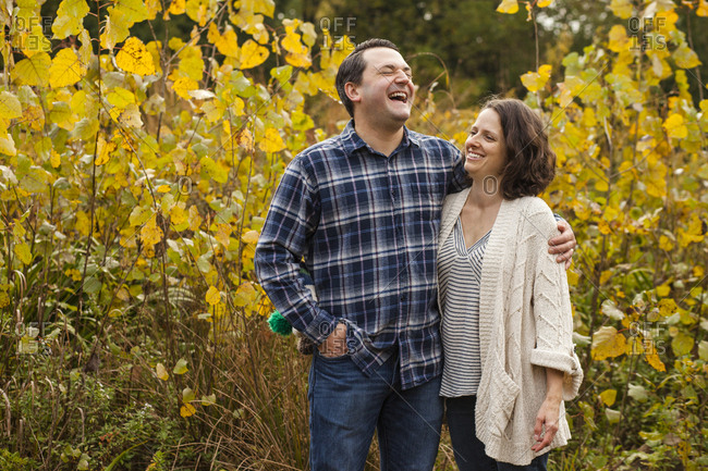 a laughing couple stand in embrace in a golden prairie