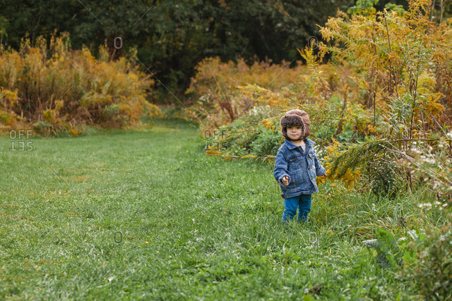 A small happy toddler stands bundled up on a grassy path in autumn