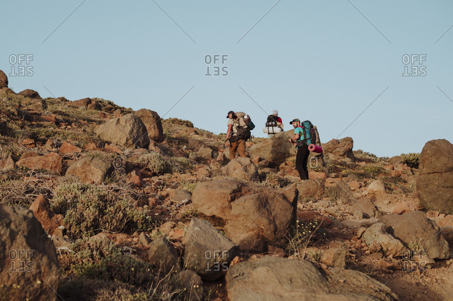 Hikers walking trough the rocks in a volcanic landscape