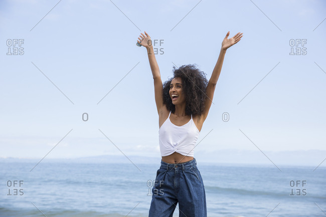 Portrait of black woman joyful with arms raised at California beach