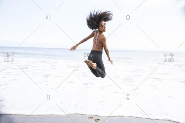 Lifestyle portrait of black woman jumping in the ocean in Los Angeles