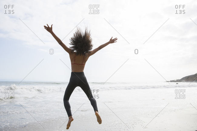 Black woman leaping with her arms out at the beach in California