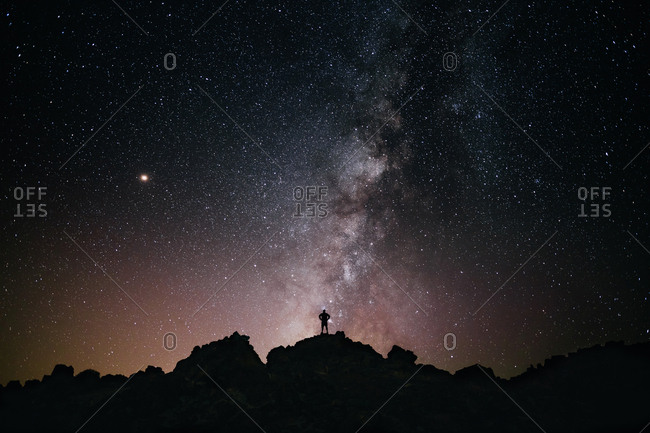 Panoramic of a person looking at the milky way