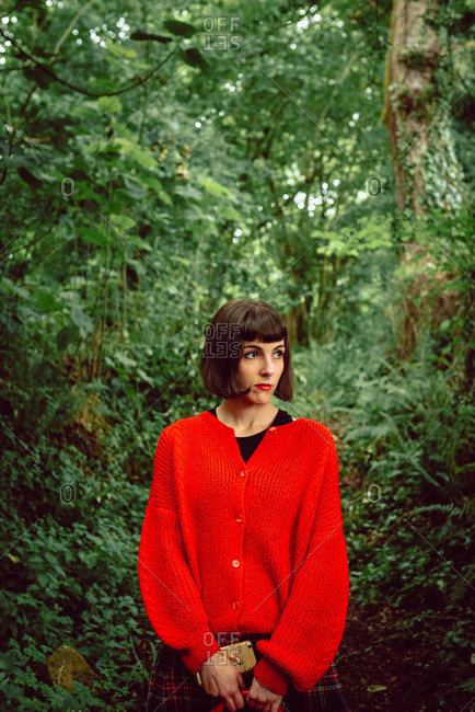 Woman in red with big red suitcase in forest