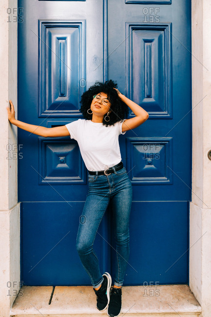 Pretty ethnic woman in white t-shirt and jeans leaning on blue door and looking up with closed eyes