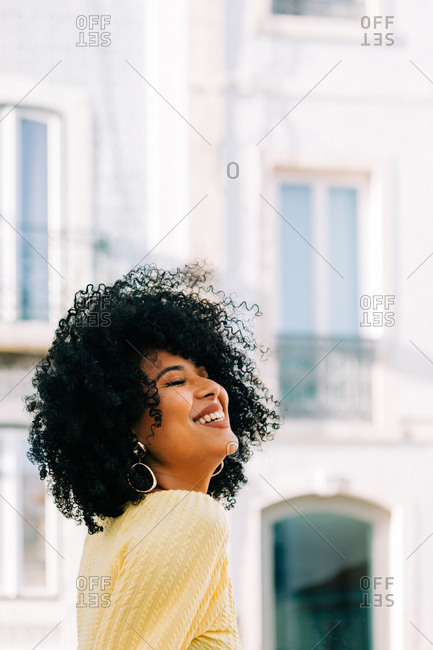 Pretty ethnic woman in yellow t-shirt and with black curly hair looking away and closed eyes on street
