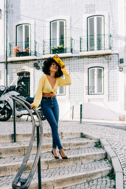 Fashionable African American woman in crop top and jeans leaning on railing and smiling with clutch in raised hand