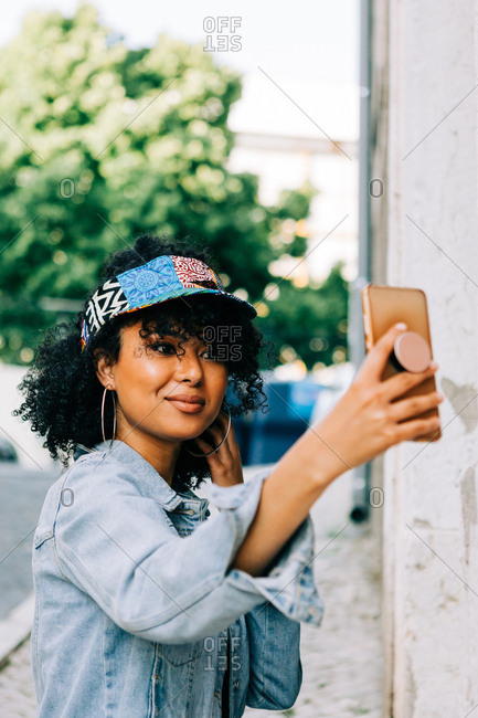 Beautiful African American woman in denim jacket and colorful cap visor standing with smartphone and taking photo in city street