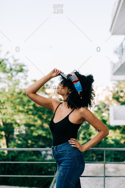 Beautiful young African American woman in jeans, tank top and headband leaning on railing and looking away