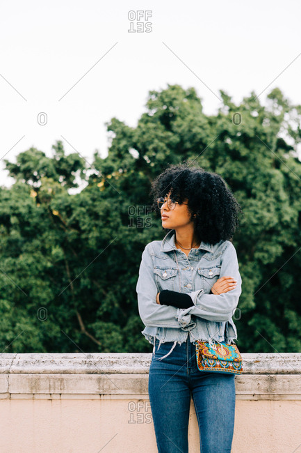Young trendy African American woman in jeans and crop top sitting on stone parapet