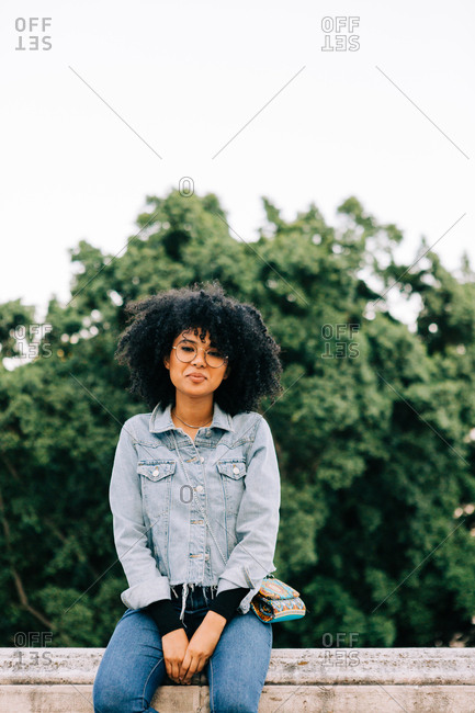 Young trendy African American woman in jeans and crop top sitting on stone parapet and looking at camera