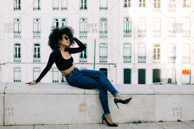 Young trendy African American woman in jeans and crop top sitting on stone parapet and looking over sunglasses