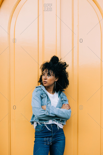 Young African American woman in jeans and denim jacket leaning on yellow door and looking away
