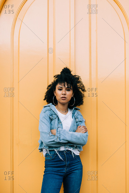 Young African American woman in jeans and denim jacket leaning on yellow door and looking at camera