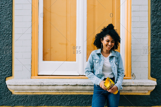 Trendy ethnic woman in jeans and denim jacket holding fashion handbag and leaning on bright windowsill outdoors