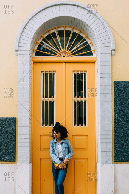 Young African American woman in jeans and denim jacket leaning on yellow door, holding clutch and looking away