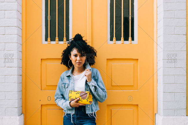 Young African American woman in jeans and denim jacket leaning on yellow door, holding clutch and looking at camera