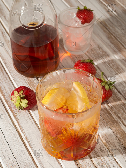 From above glass of iced drink with lemon and strawberry on rustic wooden table next to bottle in daylight