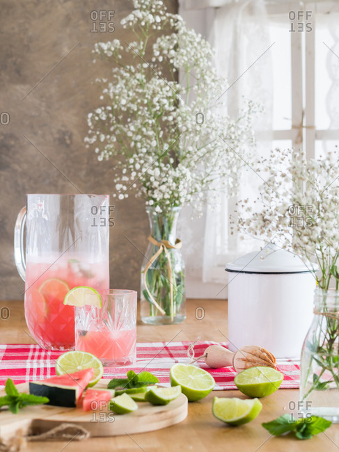 Cold glass jug of iced pink lemonade with watermelon and lime slices on rustic kitchen table next to bunch of gypsophila flowers in daylight