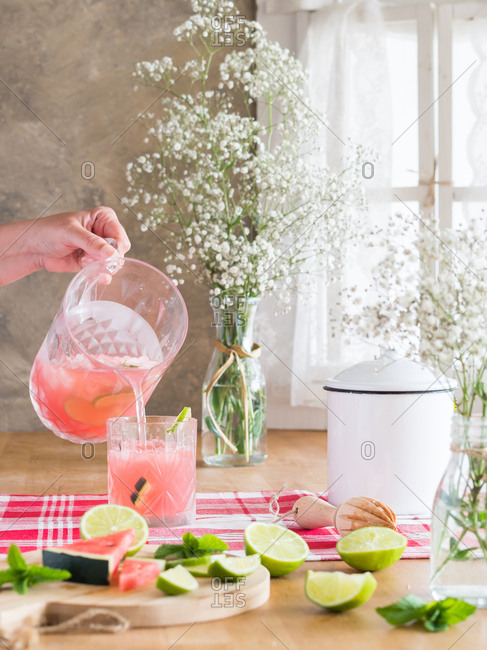 Iced pink drink with watermelon and lime slices pouring into glass from cold jar on rustic kitchen table next to bunch of gypsophila flowers in daylight