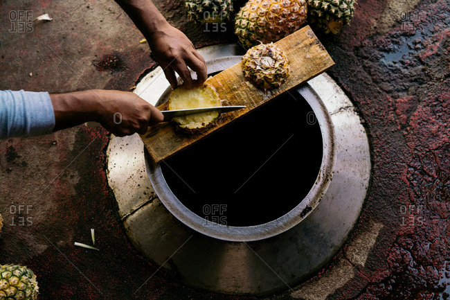 From above crop adult man chopping pineapple with knife on top of metal reservoir in daylight