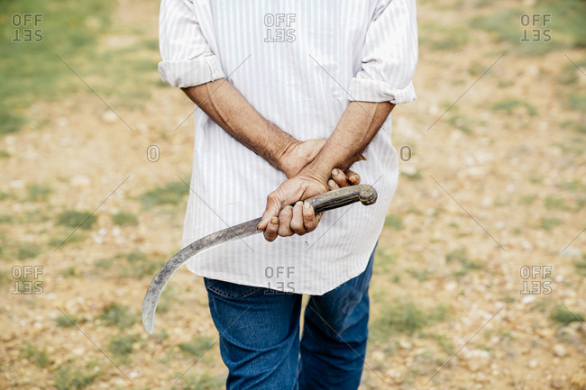Crop from behind adult casual man carrying sickle while walking along dry field in daylight