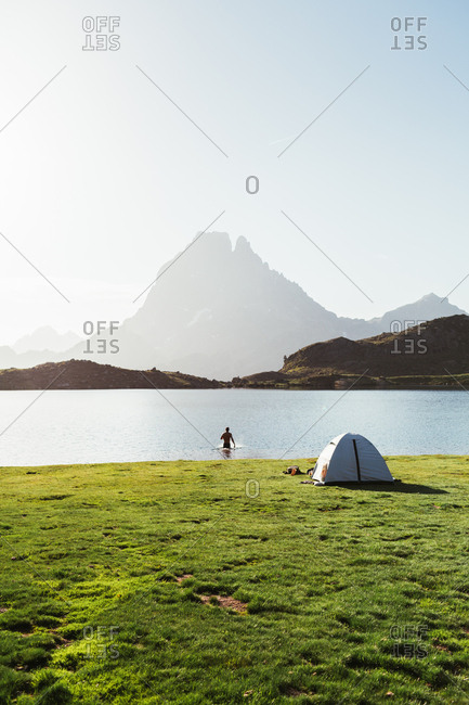 Man bathing near the tent in the mountain