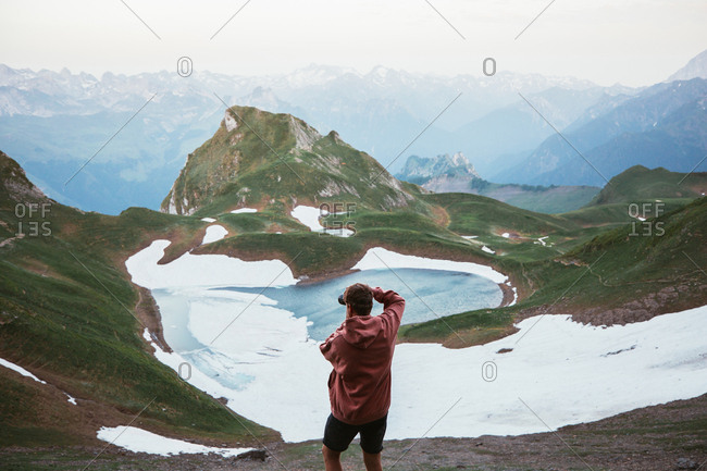 Back view of anonymous male tourist taking photo of mountain lake surrounded by snow and ridge in Pyrenees
