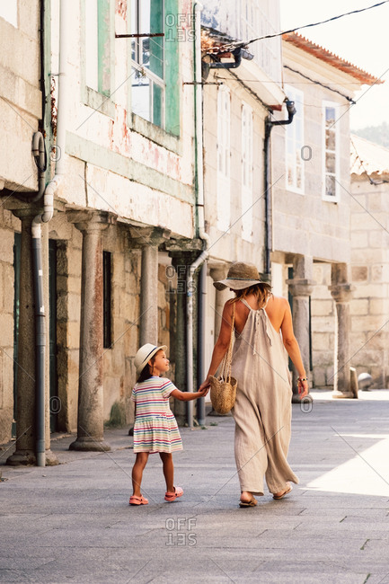 Back view of woman in hat and child walking by hand on pavement along old house on column looking at each other