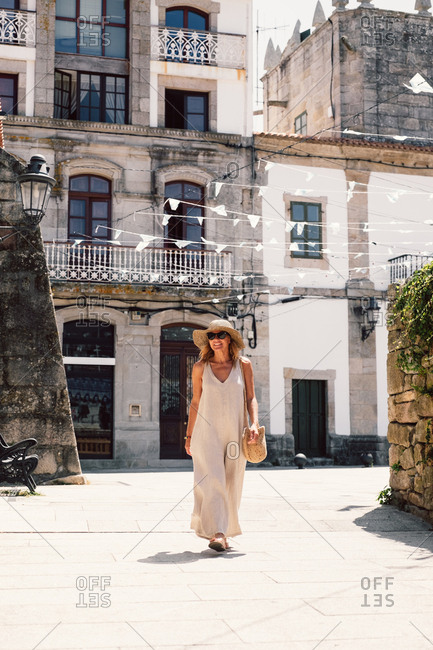 Tanned stylish woman in hat, sunglasses and light costume enjoying sightseeing in street with interesting houses in city looking away