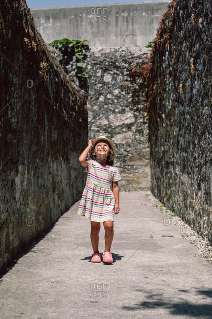 Active adorable child in hat standing on bottom of stony place in sunlight and looking up