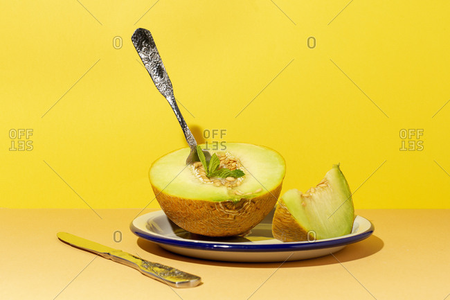 From above cut ripe appetizing sweet pitted melon on plate with spoon and fork in yellow table
