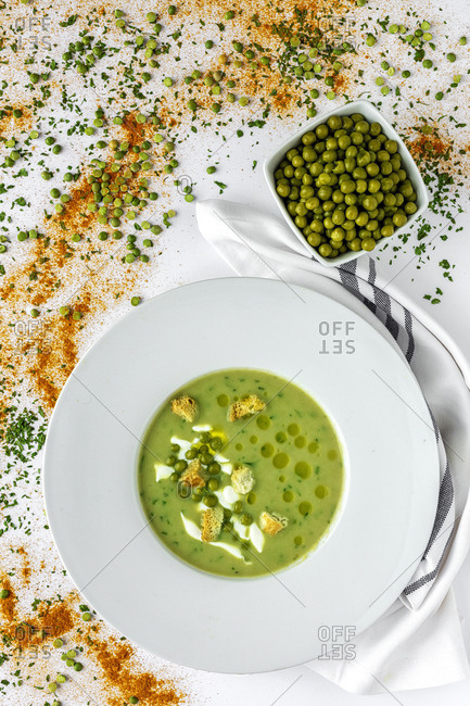 From above mashed vegetable creamy soup with small crackers and green peas in white bowl on wooden background