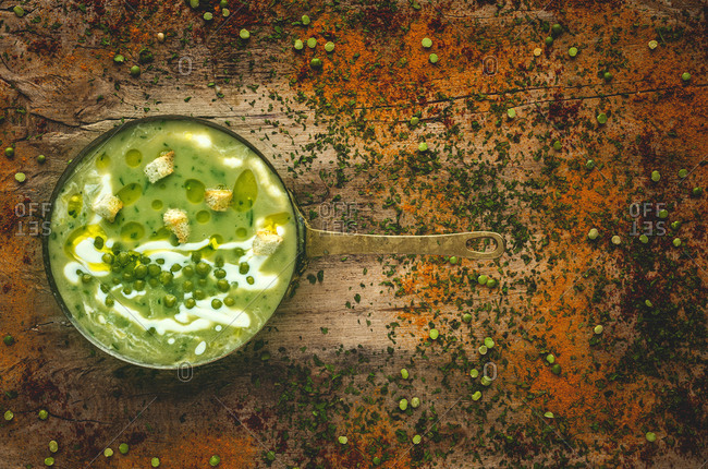 From above mashed vegetable creamy soup with small crackers and green peas on pan on wooden background