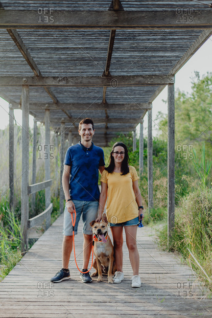 Happy adult couple standing with dog at countryside